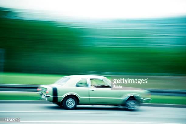 Classic car speeding down road,