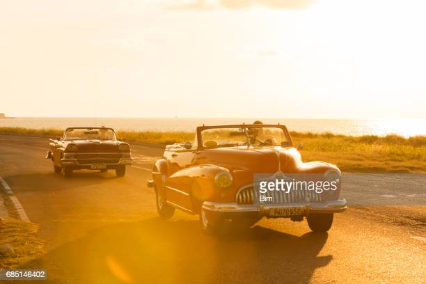 classic cars driving along the coast in cuba - collector's car stock photos and pictures