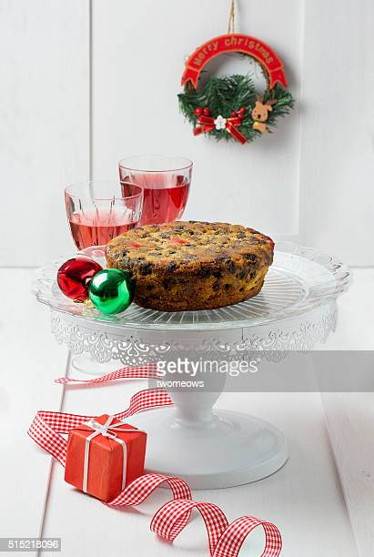 Classic Christmas fruit cake with two crystal wine glasses with red wine on Christmas party table top.