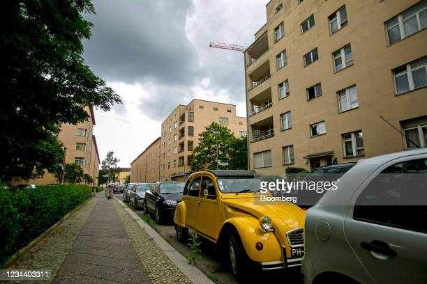 Classic Citroen 2CV automobile parked outside residential apartment blocks on the Carl Legien modernist housing estate, operated by Deutsche Wohnen...