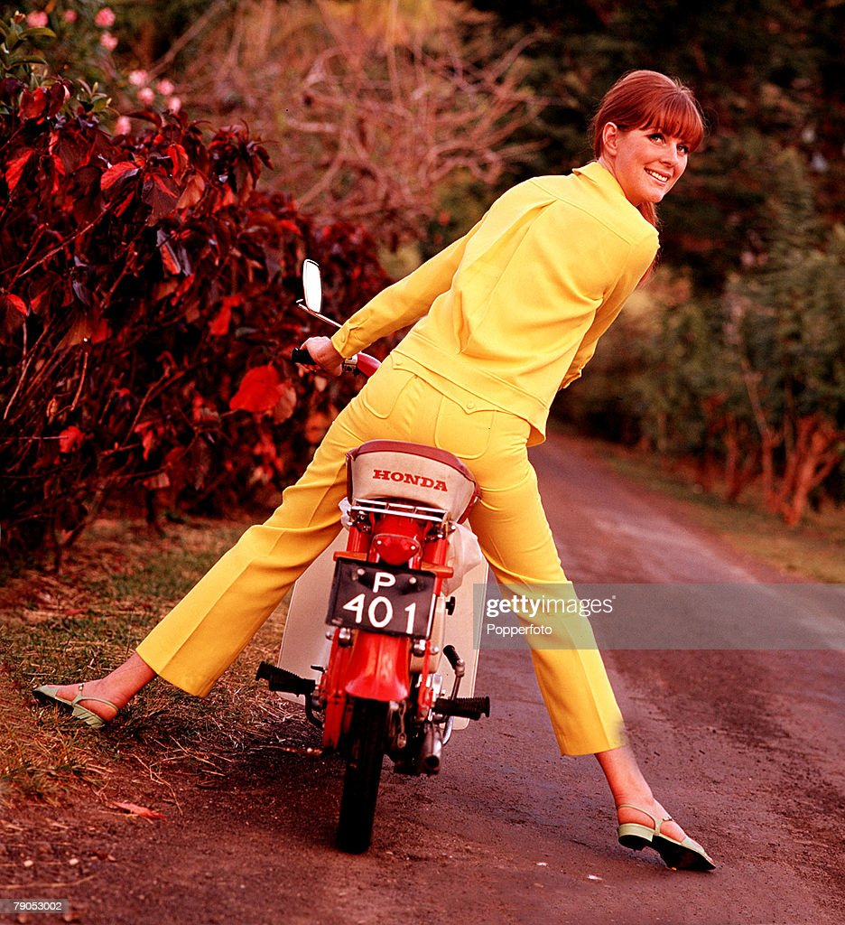 Classic Collection, Page 112, 10416305, A back view of a woman dressed in a yellow suit, on a moped, looking back towards the camera