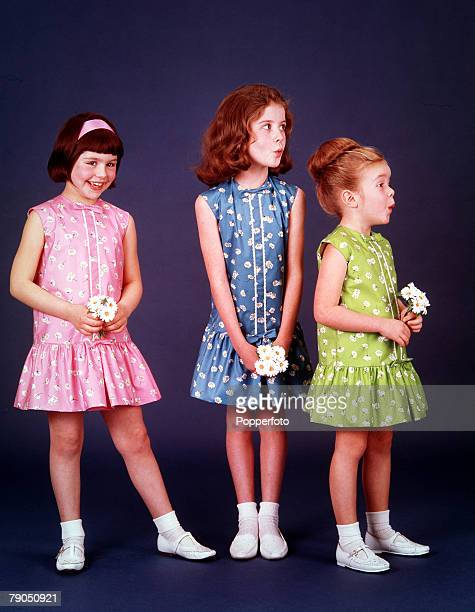 Classic Collection Page 12 Studio portrait of three girls in flowery dresses white shoes and ankle socks pulling faces and holding flowers