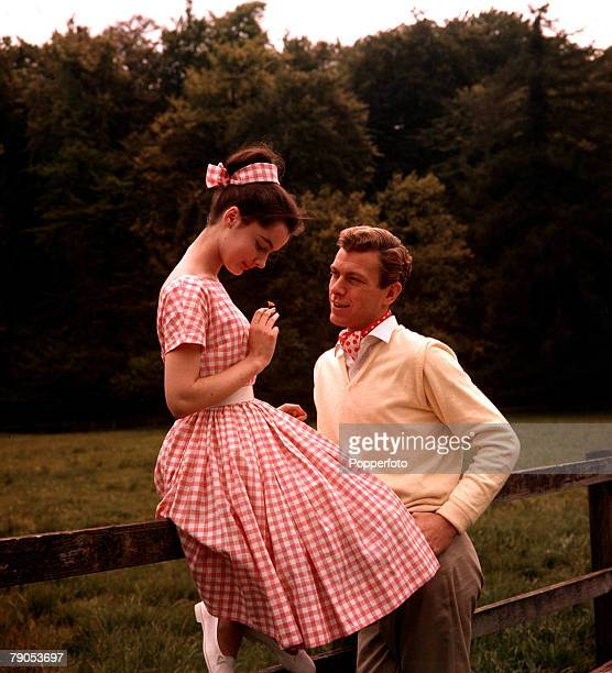 Classic Collection Page 124 A woman in a pink gingham dress sitting on a fence looking down at her hand while man in a yellow jumper smiles up at her...