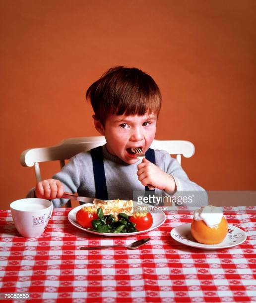 Classic Collection Page 15 A little boy sitting at a table eating his dinner With glass of milk and red gingham table cloth