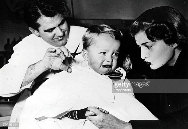 16 A mother tries to comfort her baby boy as he cries whilst having his hair cut by the barber
