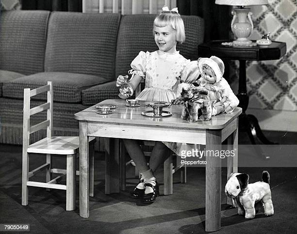 27 A young blonde girl sitting at a childs table having a tea party with her toy dolls teddy bear and soft dog