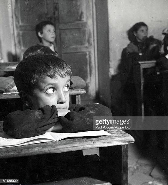 34 Italy School A young boy with wide eyes sitting at his desk in class