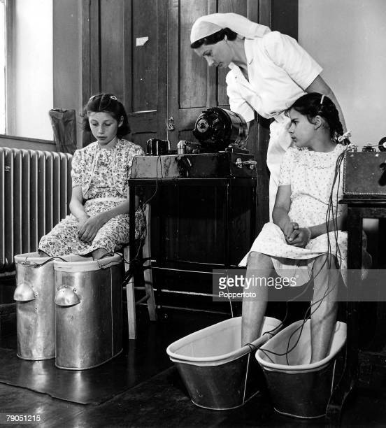 Classic Collection Page 53 Bristol July 1948 Two apprehensive looking girls with their feet in baths receive treatment from a nurse in Bristol health...