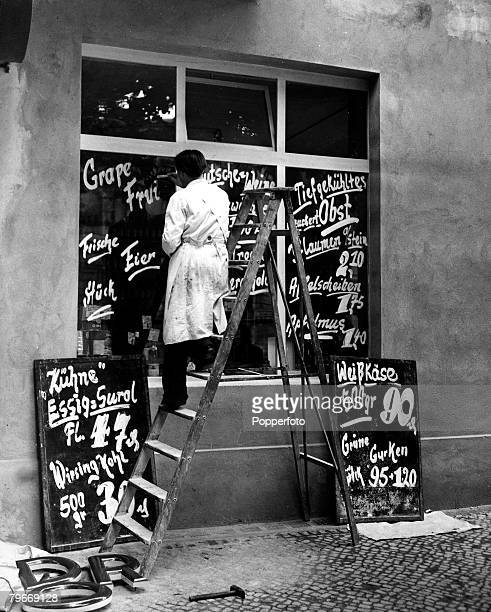 Classic Collection Page 59 Shopkeeper on ladder painting signs on his shop window Berlin June 1949
