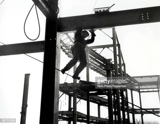 Classic Collection Page 66 Construction worker balances precariously on a suspended wire while steadying himself by holding on to an overhead steel...