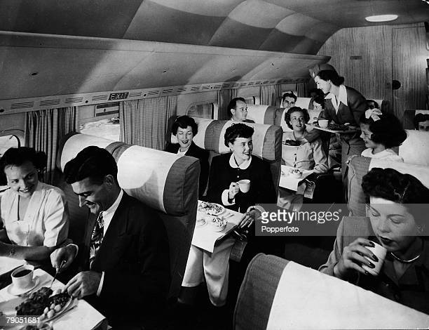Classic Collection Page 77 Shot of passengers in an aeroplane being served food by an airhostess