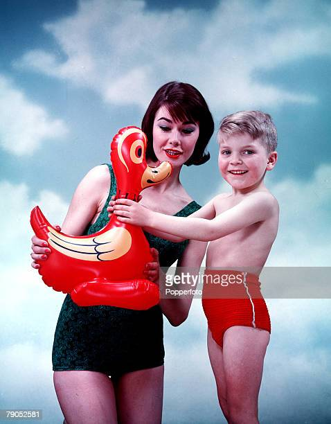 Classic Collection Page 78 Studio portrait of woman in green swimsuit with smiling young boy in swimming costume and inflatable duck