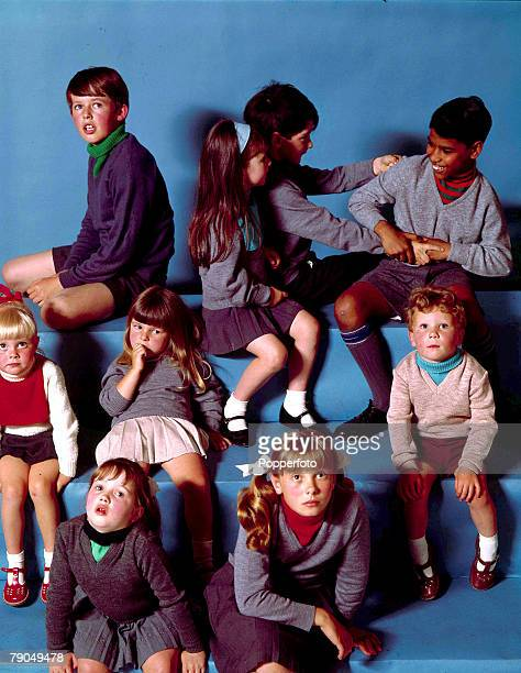 Classic Collection page 8 Childrens Fashion 1964 Group of nine boys and girls wearing various grey knitted jumpers Sitting in a studio on steps...