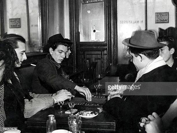 Classic Collection Page 84 Group of young people drinking and playing cards in the famous bar frequented by artists opposite the Academy des Beaux...