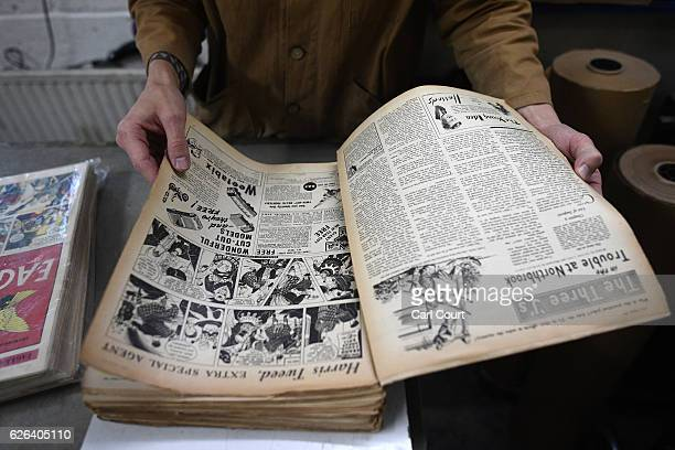 A classic comic is handled before being stitched to other comics to be bound into a book by bookbinder Patrick Kidder at Collis Bird and Withey...