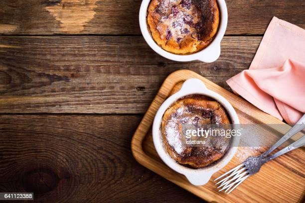 Classic french dessert cherry clafoutis in ceramic ramekins