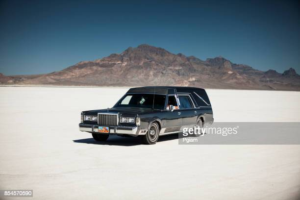 Classic funeral hearse drives on the salt flats in Utah USA