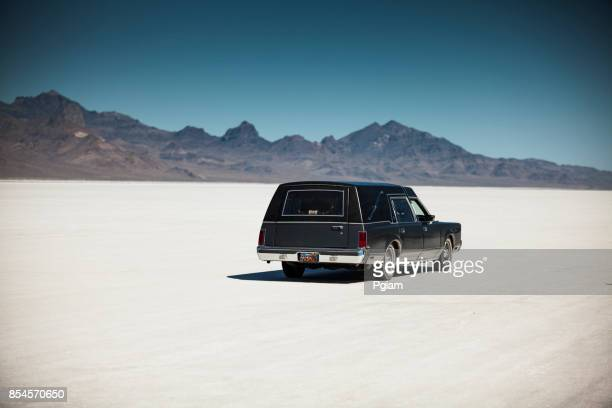 classic funeral hearse drives on the salt flats in utah usa - hearse stock photos and pictures