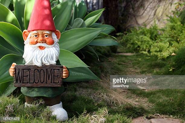 classic garden gnome with welcome sign - fairy stock photos and pictures