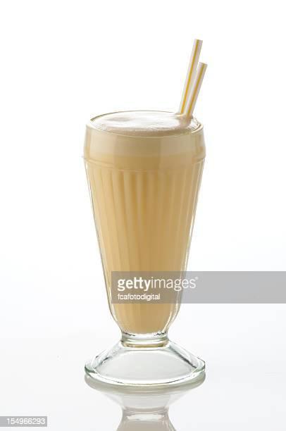 Classic glass of vanilla milk shake on white backdrop.