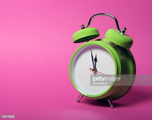 Classic green alarm clock on vibrant pink background