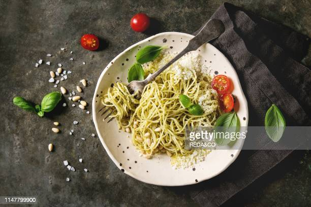 Classic italian spaghetti pasta with pesto sauce pine nuts olive oil and fresh basil Served in ceramic plate with fork and ingredients above over...
