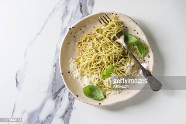 Classic italian spaghetti pasta with pesto sauce pine nuts olive oil and fresh basil Served in ceramic plate with fork over white marble background...