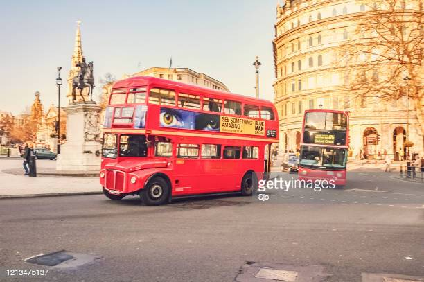 """classic london double decker bus and modern london bus driving around a corner at trafalgar square in london on a sunny autumn day - """"sjoerd van der wal"""" or """"sjo"""" stock pictures, royalty-free photos & images"""