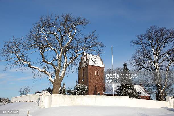 Classic Medieval parish church in snow covered winter landscape