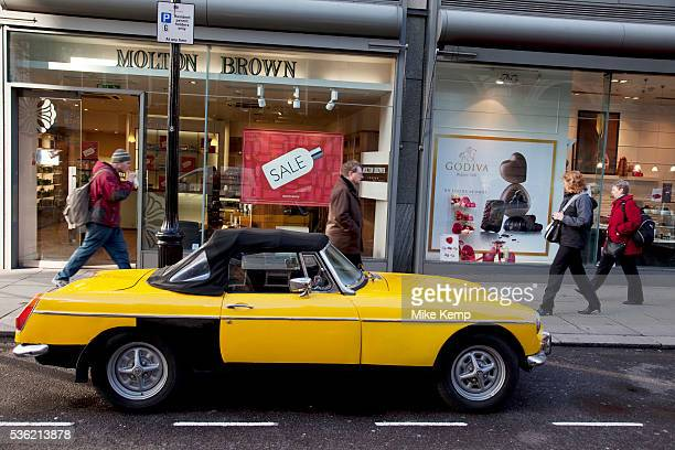 Classic MGB Midget car parked on a London street Bright yellow this little sports car is an icon in motor vehicle history