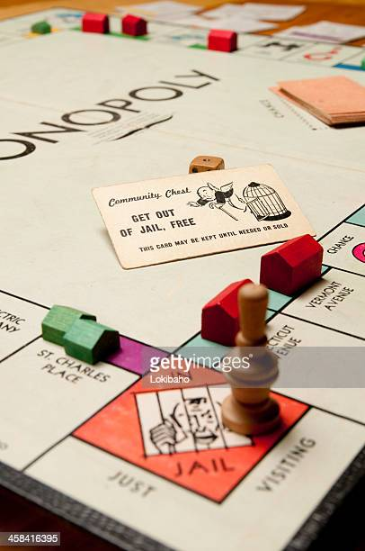 classic monopoly game with wood pieces - game night stock photos and pictures