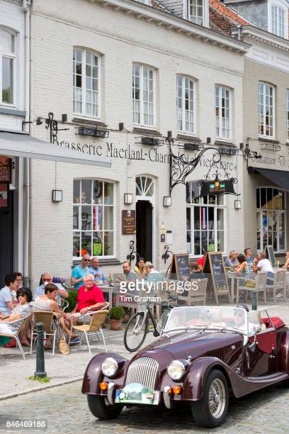 Classic Morgan drop head sports car being driven past diners al fresco at restaurant in Kerk Straat Damme Belgium