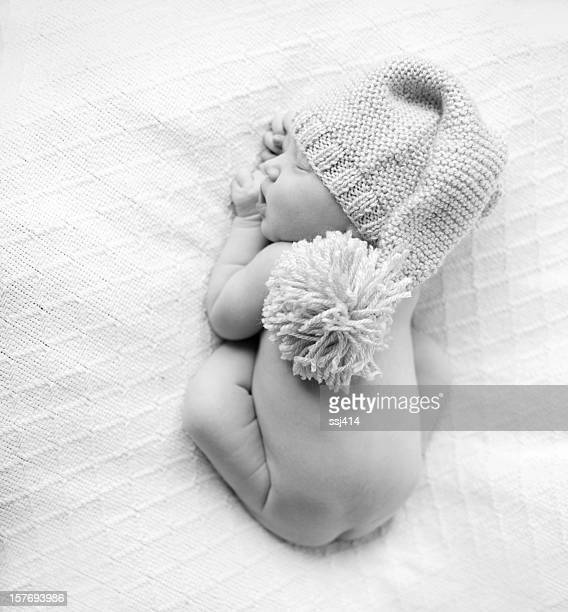 classic newborn laying on belly curled up with hat - lying on front stock pictures, royalty-free photos & images