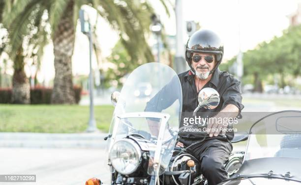 classic old sidecar senior biker in city bulevar - southern european descent stock pictures, royalty-free photos & images