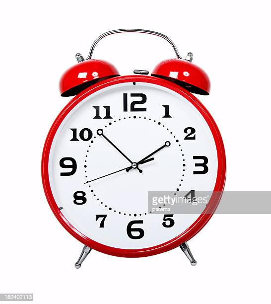 A classic, red alarm clock showing a time of 1:52