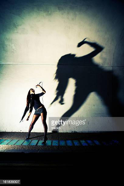 Classic rock pose and shadow from a confident young woman