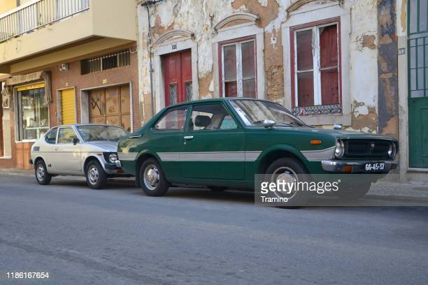 classic toyota corolla and suzuki cervo cx-g parked on the street - faro city portugal stock photos and pictures