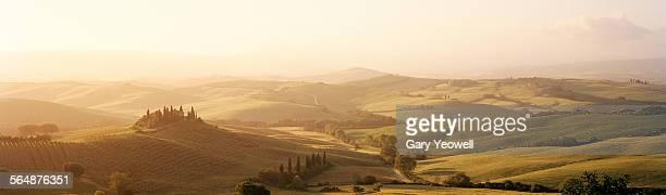 Classic Tuscan landscape with farmhouse at sunrise