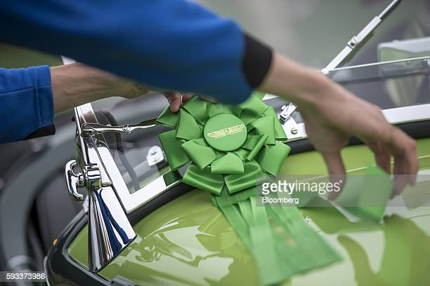 A classic vehicle owner places a green rosette on the hood of a 1935 BMW 315/1 Roadster motor vehicle manufactured by Bayerische Motoren Werke AG...