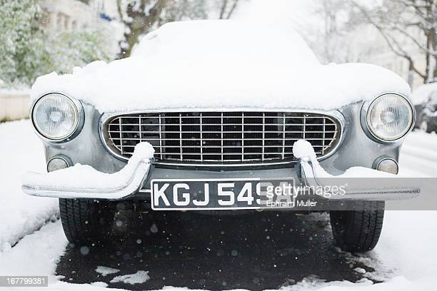 "Classic vintage car submerged in snow during ""Beat from the East"" cold front in London in January"