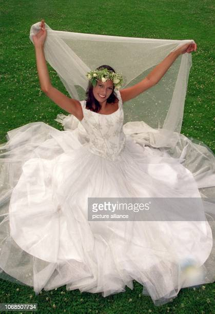 A classic wedding dress in white with several layers and a flower headpiece photographed on 12 July 1999 Back in the 1990s couples were determined to...