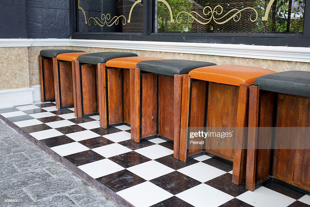 Classic wooden bar stools are lined up at an outdoor bar. : Stock Photo