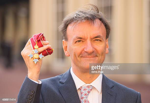 Classical concert pianist Stephen Hough poses with his CBE medal awarded during an investiture ceremony at Buckingham Palace on October 9 2014 in...