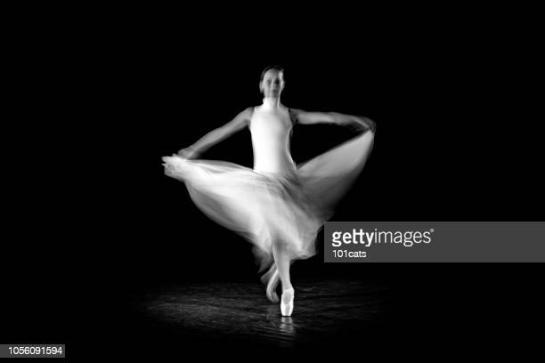 classical dancer dancing on the lack background with white dressed