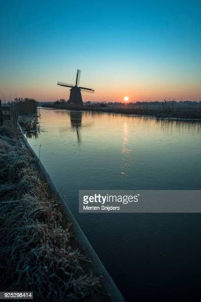Classical dutch windmill amidst frozen countryside