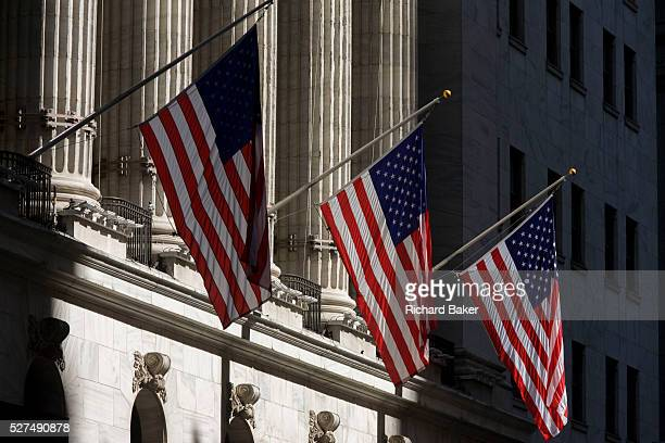 Classical pillars and American flag hanging in front of the New York Stock Exchange on Wall Street Lower Manhattan This famous street symbolises the...