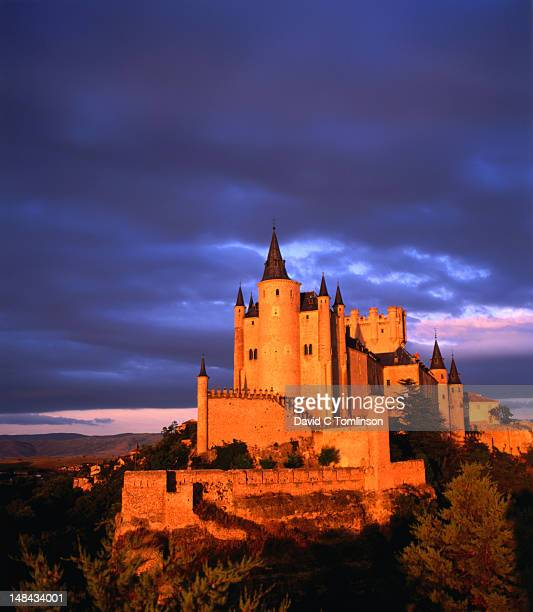 Classical view of Alcazar Castle on hilltop, overcast skies and sunset glow.