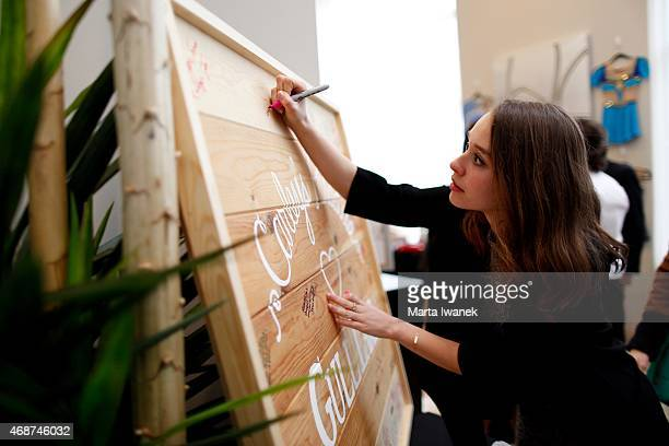 APRIL 4 Classmate Ana Zdravkovic signs a wooden board that will be placed at Carley Allison's cottage during a gathering of friends and family to...