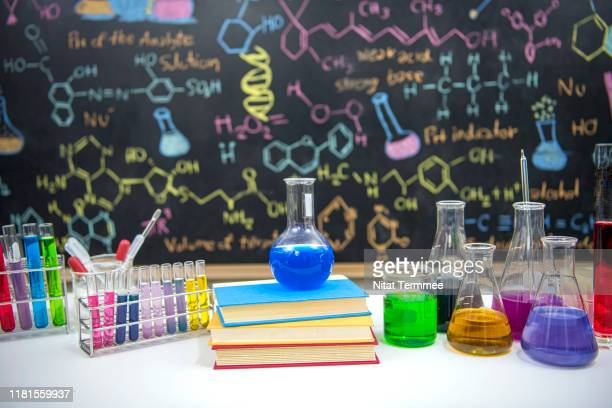 classroom desk and drawn formula on blackboard of chemistry teaching with books and instruments. - physics stock pictures, royalty-free photos & images
