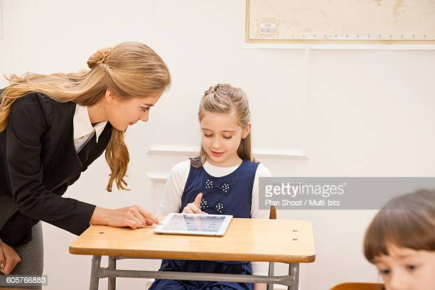 classroom desks and children - teacher bending over stock photos and pictures